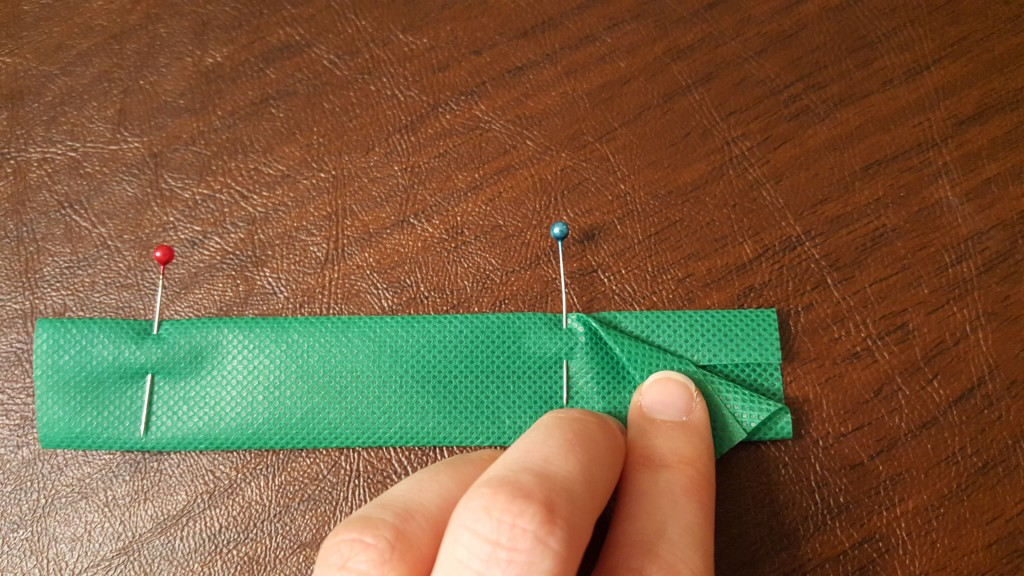 """Pin under 1/4"""" on each side of the strap and fold in half."""