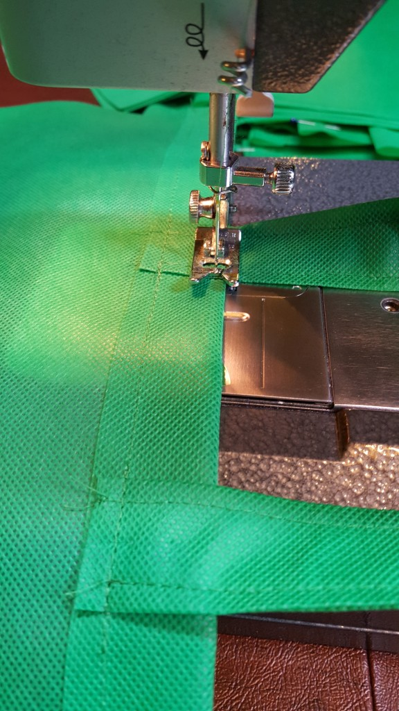 Stitch handles to the bag sewing close to the top and bottom of the reinforcement strip.